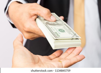 businessman in suit gives dollors US to a man