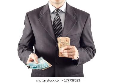 A businessman in a suit giving brazilian money