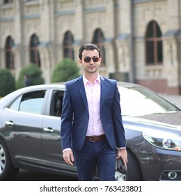 Businessman in a suit and glasses is moving away from the car in the street