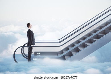 Businessman in suit going up by escalator among white clouds. Road to success concept