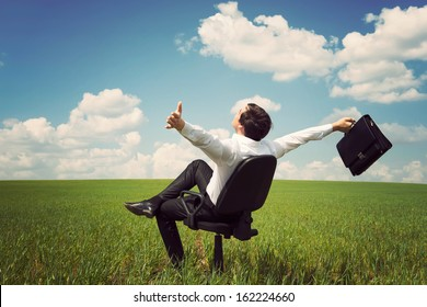businessman in a suit in a green field with a blue sky sitting on an office chair and waving his arms