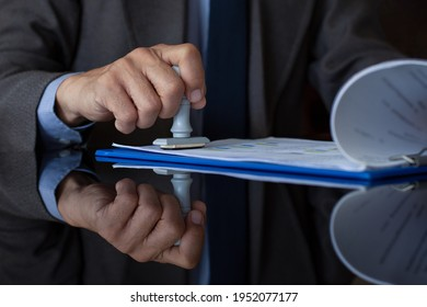Businessman in suit hand stamping rubber stamp on document at office. Authorized allowance permission approval concept.