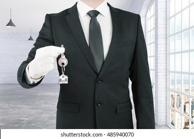 Businessman in suit handing key with house keychain on white brick interior background. Real estate and mortgage concept