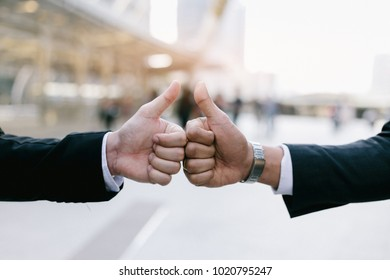Businessman in suit handshake together for successful in city and walking people background.