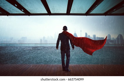 Businessman in a suit and hero cape stands at sky garden ,victory concept. cityscape background , raining day.