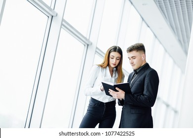 A businessman in a suit and his assistant discuss plans for the day at the office near the window. A man records information in a notebook.