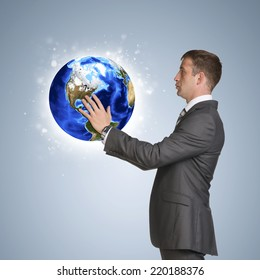 Businessman in suit hold Earth. Elements of this image are furnished by NASA