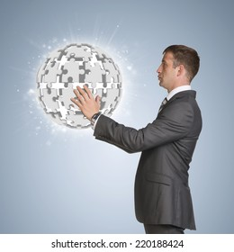 Businessman in suit hold and jigsaw puzzle sphere