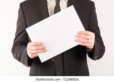Businessman in suit holding blank paper isolated centered on white background