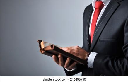 Geschäftsmann in einem Anzug, der ein Buch hält