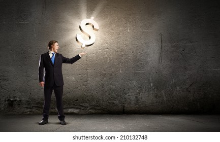Businessman in suit holding dollar sign in palm