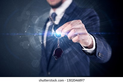 Businessman in suit holding over a key with connection concept around