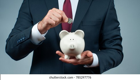 Businessman in suit is holding piggy bank. Finance Savings concept