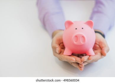 Businessman in a suit holding pink piggy bank with both hands, isolated on white background.