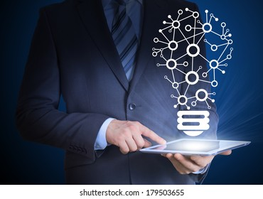Businessman in a suit holding a tablet in his hands. Above the screen tablet icons links in the form of light bulb