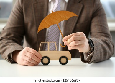 Businessman in suit holding umbrella in hand. Car concept