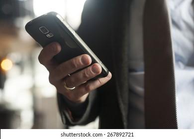 Businessman in suit, jacket,shirt, tie, using his smart phone