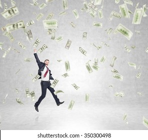 businessman in a suit jumping happily with his hand up, money falling from above, concept of success