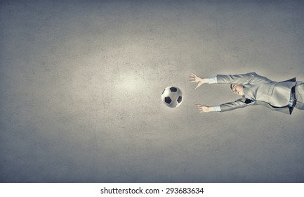 Businessman in suit jumping to hit soccer ball