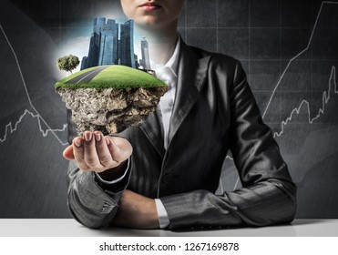 Businessman in suit keeping green island with skycraper city in hands with business sketches on background.