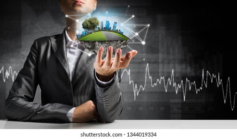 Businessman in suit keeping green island with skycraper city with network connections in hand with dark background.