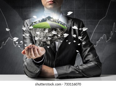 Businessman in suit keeping green island with skycraper city and flying paper planes in hands with business sketches on background.