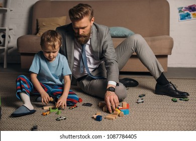 businessman in suit and little son playing with wooden blocks on floor at home, work and life balance concept