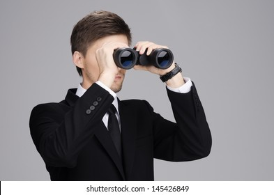 Businessman in suit looking through a binoculars with gray  background