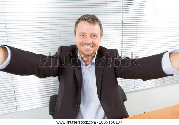 businessman in a suit makes a selfie at desk