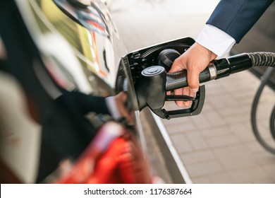 A businessman in a suit manages his car with gasoline at a gas station. Hand and black refueling gun close-up.
