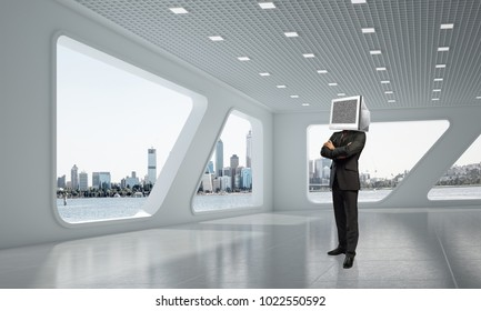 Businessman in suit with monitor instead of head keeping arms crossed while standing inside office building. 3D rendering.