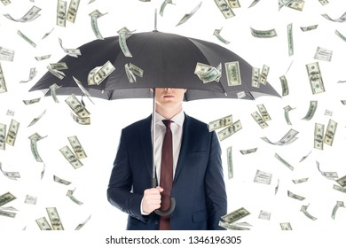 businessman in suit with obscure face and umbrella under money rain