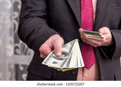 Businessman in suit offer dollar banknotes, close up