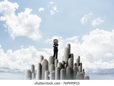 Businessman in suit with an old TV instead of head keeping arms crossed while standing on the top of stone columns with beautiful landscape on background.