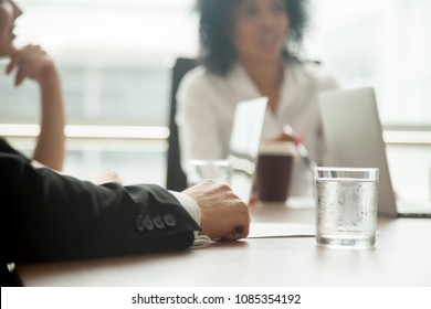 Businessman in suit participating diverse group meeting or negotiations concept, business partner attending office executive board briefing or workshop, male hand on conference table close up view