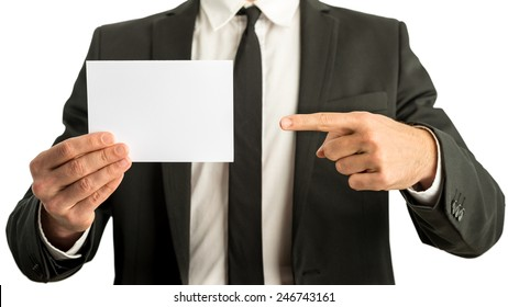 Businessman in a suit pointing to a blank white rectangular card that he is holding in his other hand ready for your text, closeup view of his hands and chest.