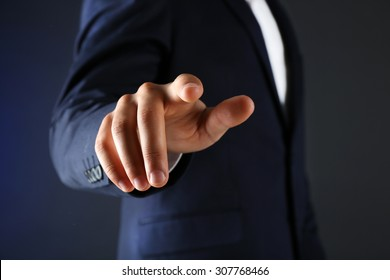 Businessman in suit points on something on dark background