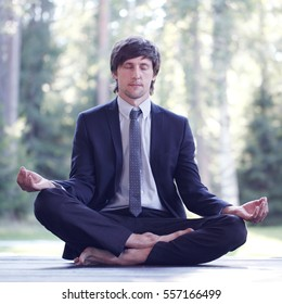 Businessman in suit practicing yoga in park