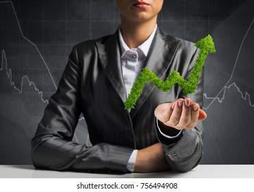 Businessman in suit presenting green plant in form of growing graph in hands with business sketches on background.