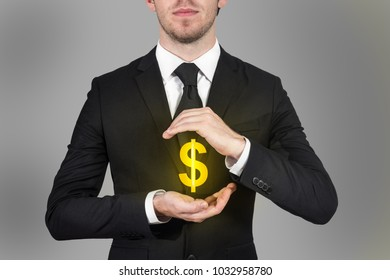 businessman in suit protecting golden dollar symbol with hand gesture