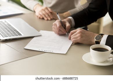 Businessman in suit puts signature on contract at business meeting after negotiations with businesswoman, male hand signs official document, subscribes name on legal binding agreement, close up view