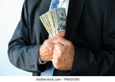 A businessman in a suit putting money in his pocket  on white background
