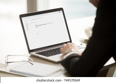 Businessman in suit reading short corporate email on laptop screen. CEO browsing message about promotion, highlights of new business deal, important reminder. Rear view over shoulder, focus on screen.