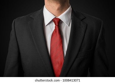 Businessman in suit with red tie on black background