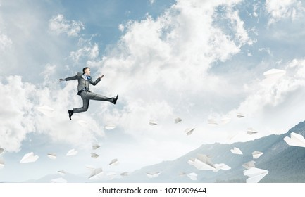 Businessman in suit running in the air among flying paper planes as symbol of active life position. Skyscape and nature view on background. 3D rendering.