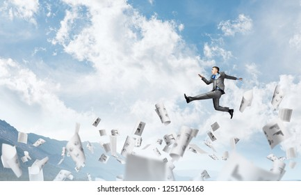 Businessman in suit running in the air among flying papers as symbol of active life position. Skyscape and nature view on background. 3D rendering.