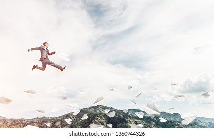 Businessman in suit running in the air among flying paper planes as symbol of active life position. Skyscape with sunlight and nature view on background. 3D rendering.