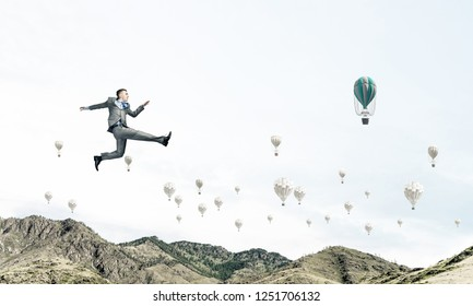 Businessman in suit running in the air as symbol of active life position. Skyscape with flying balloons and nature view on background. 3D rendering.