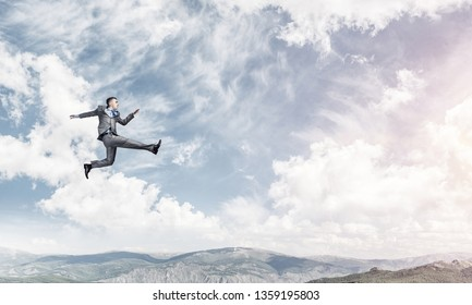 Businessman in suit running in the air as symbol of active life position. Skyscape with sunlight and nature view on background. 3D rendering.