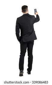 Businessman in suit searching for good phone signal rear view or taking photo. Full body length portrait isolated over white studio background.